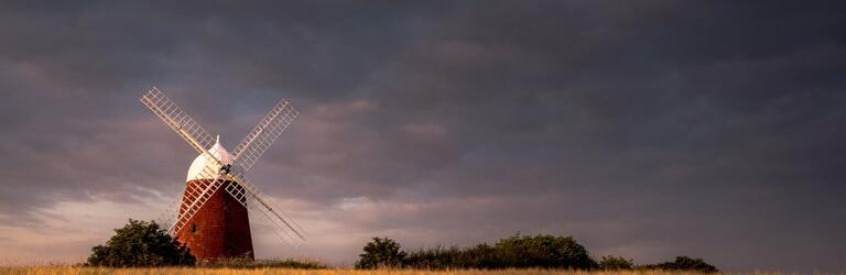 Artistic photo of Halnaker windmill under dark skies, by local photographer Jamie Fielding
