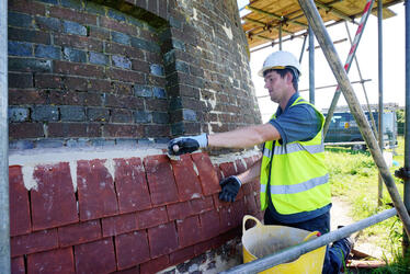 Photograph of a younger tradesman learning how to restore heritage buildings